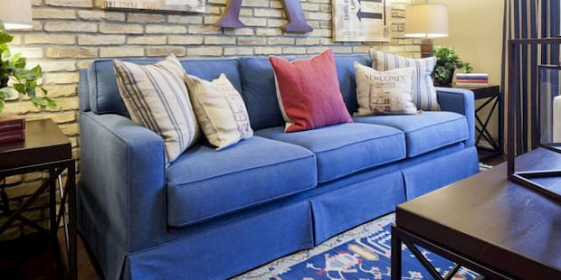 blue sofa with pillows on it and wooden table