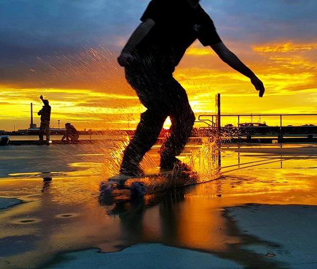 guy cruising e-board through water