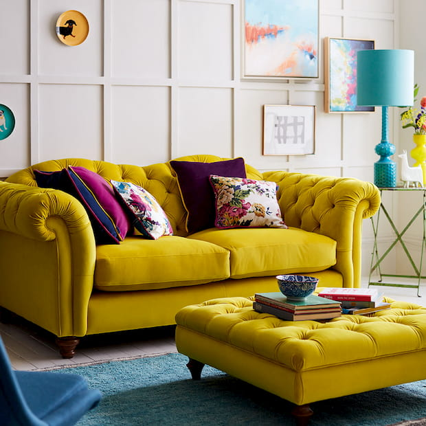 modern yellow sofa for two with colorful pillows on it