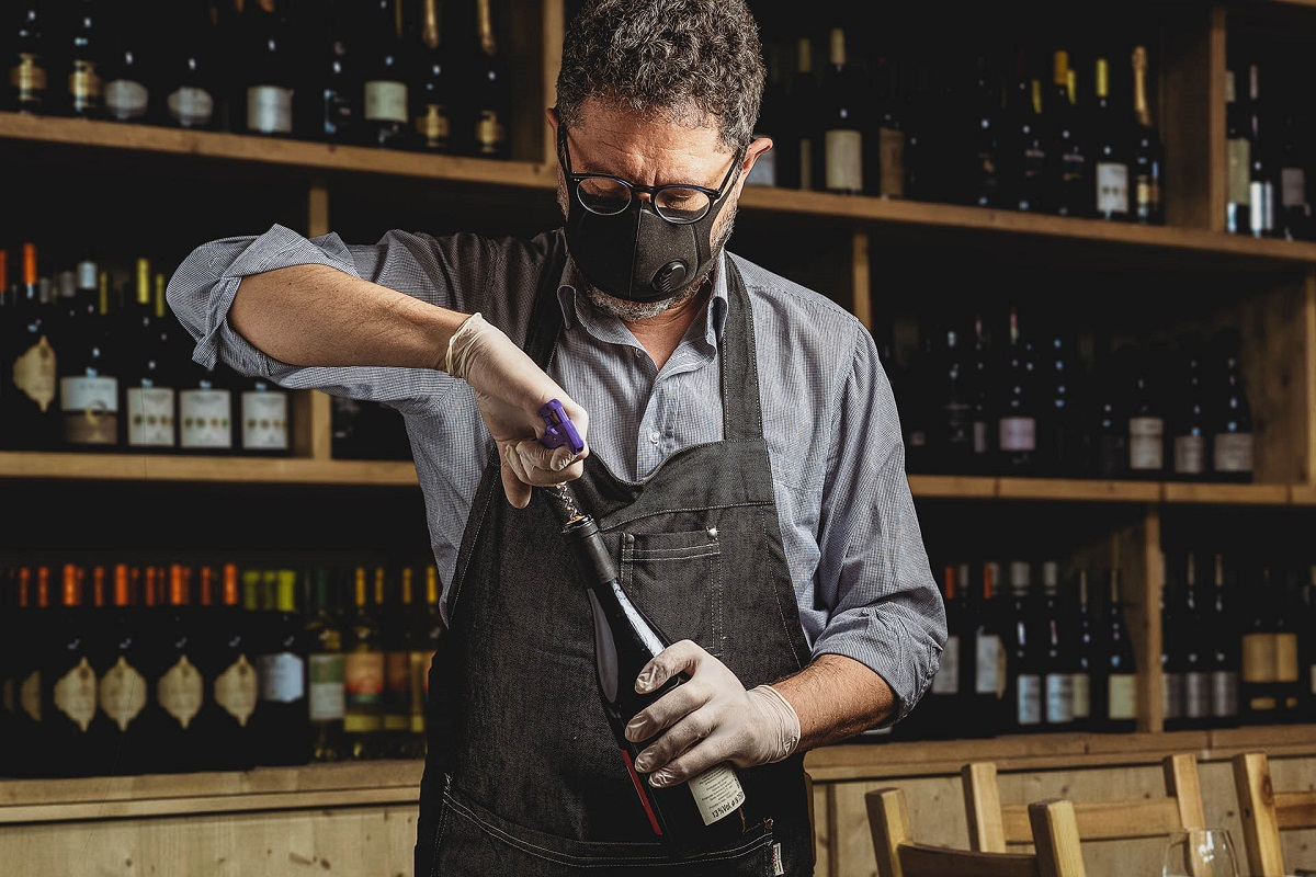 a bartender opens a bottle of red wine wearing a protective mask due to the coronavirus pandemic. Safety reopening of restaurants after the covid-19 lockdown.