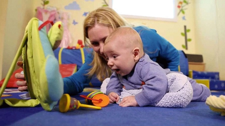 picture of a woman and a baby on the floor playing